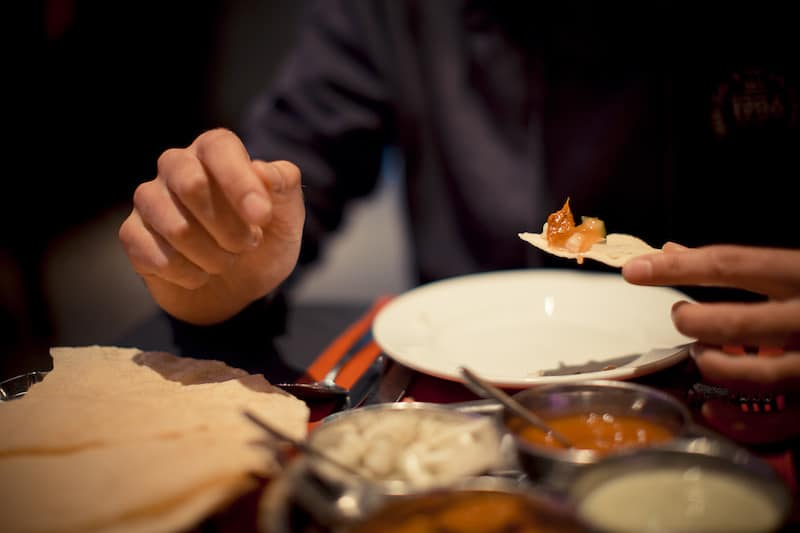 Our man smashes in to the poppadum and chutney at Passage to India Whitby