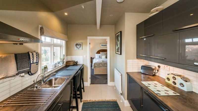 The kitchen of Pebble Cottage leads to the bedroom
