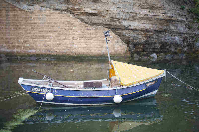 A fishing coble bobs in the water at Staithes
