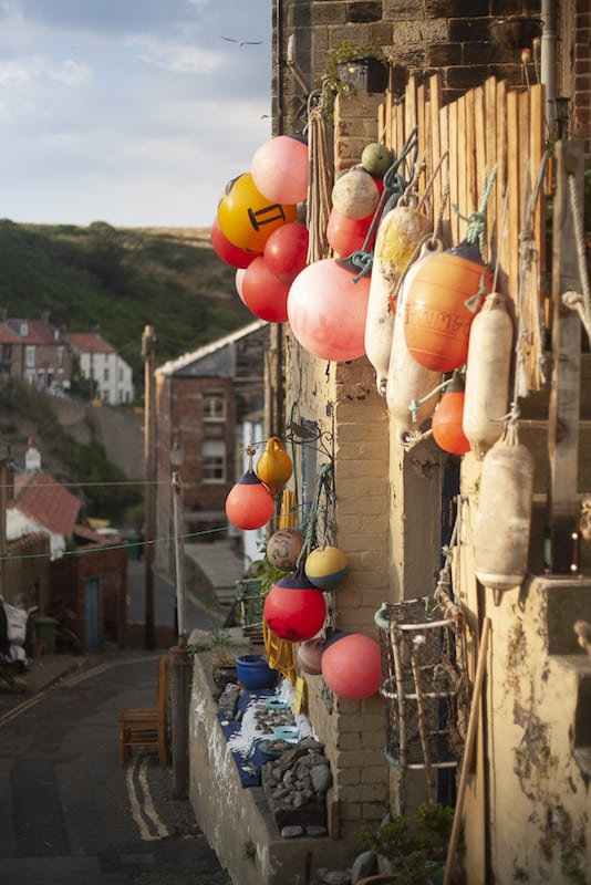 Buoys and jet outside a Fishermans Cottage in Staithes during Staithes Festival