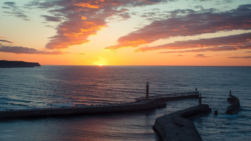 Sun sets in to the sea over Whitby pier at summer solstice